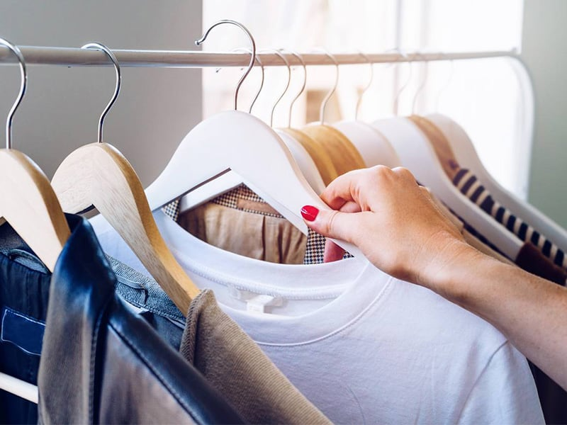 a woman's hand holding up an item clothing from a clothing rack