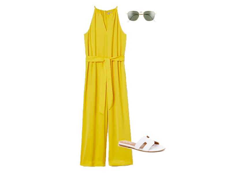 yellow jumpsuit, white sandals, and gold ray ban sunglasses
